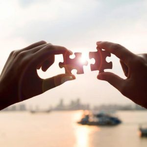 Bild für die NLP Ausbildungen. Zwei Hände stecken zwei Puzzlestücke zusammen. Im Hintergrund ist eine Fluss und eine Stadt unscharf zu erkennen.