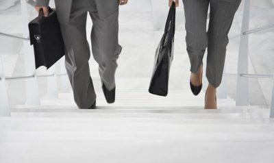 Bild für den Entwicklungs- und Karrierecoach. Mann und Frau in Businessoutfit laufen eine Treppe hoch. Nur die Füße und Taschen sind zu sehen.