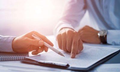 Bild für die Ausbildung Zertifizierung zum Reiss Motivation Profile® Master. Zwei Personen schauen auf ein beschriftetes Papier. Ein Mann zeigt mit dem Finger darauf, der andere folgt mit einem Kugelschreiber.