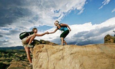 Bild für den Systemischer Business Coach Ausbildung. Zwei Frauen beim klettern. Eine hilft der anderen hinauf