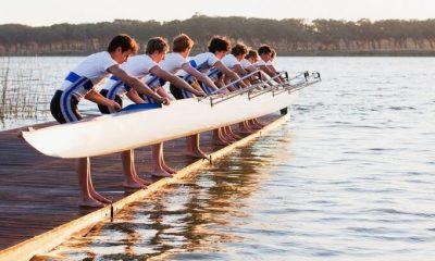 Bild für die Team Coach Ausbildung. Eine Gruppe von Jungs steht am Steg und lässt ein Kajak zu Wasser